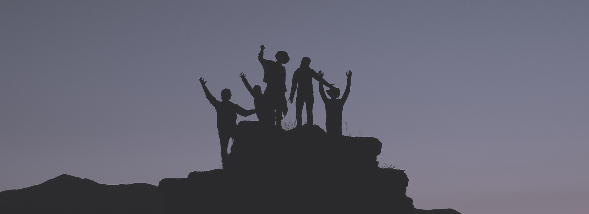 Silhouettes of people cheering at top of mountain